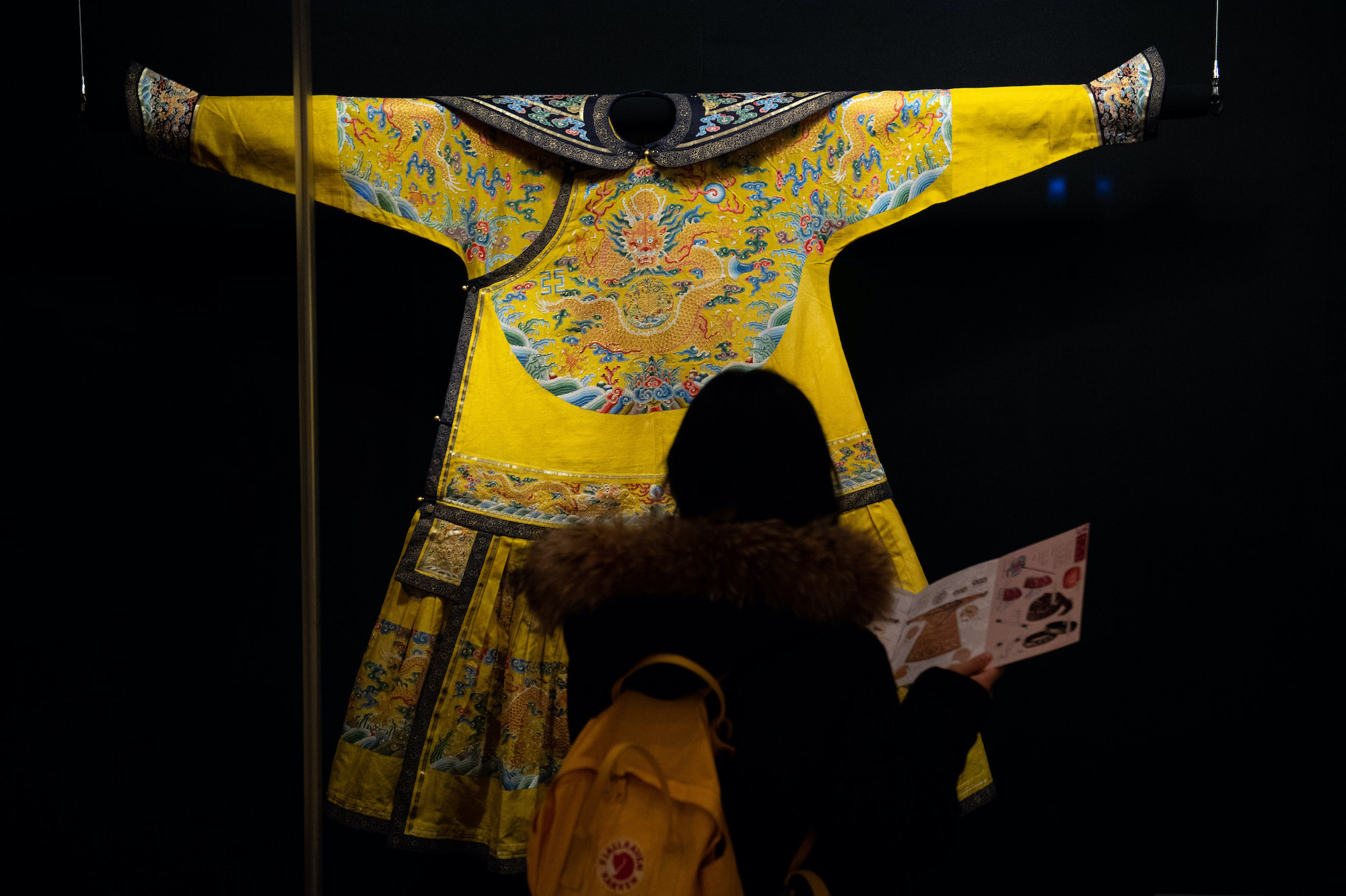An audience looks at one of the costumes in the exhibition | Photo by Xinhua News Agency/Cheong Kam Ka