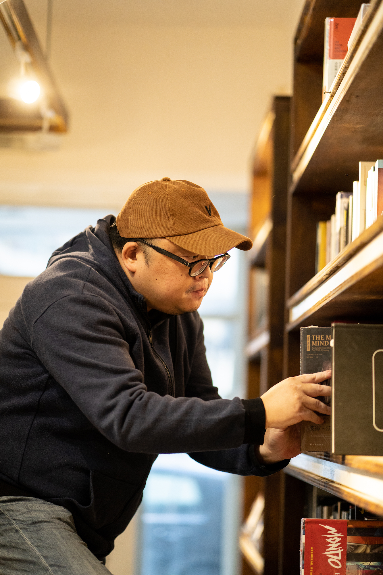 Anson Ng, owner of Pin-to Livros & Musica, shelving books