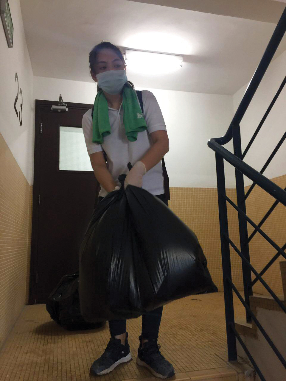 Emma Chan takes a trash bag down flights of stairs to help the elderly | Photo Courtesy of Emma Chan