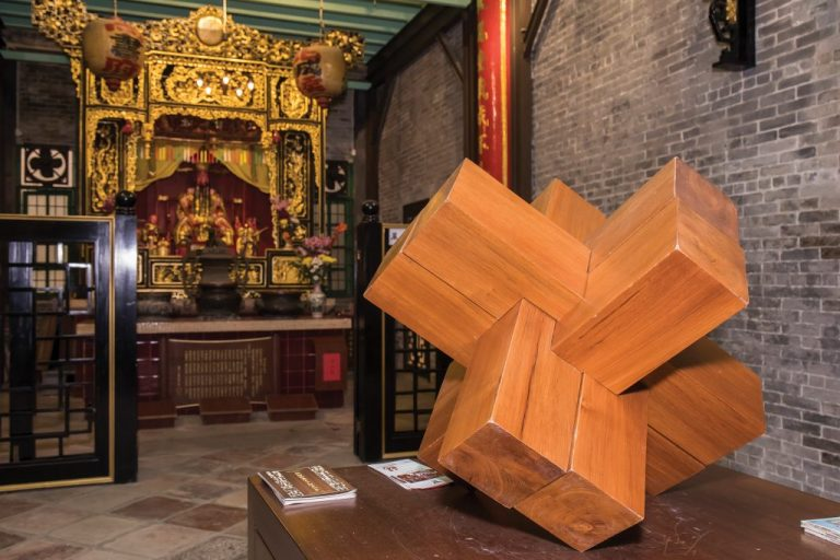 A large wooden Lu Ban lock is displayed in front of an altar, right next to the entrance to the Exhibition Room of Master Lu Ban's Woodcraft Works | Photo by António Sanmarful