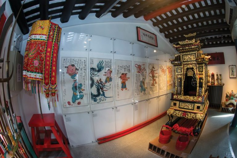 The iconic sedan chair in front of illustrations of Na Tcha by cartoonist Ah-Cheng inside the Na Tcha Exhibition Room - Photo by Eric Tam