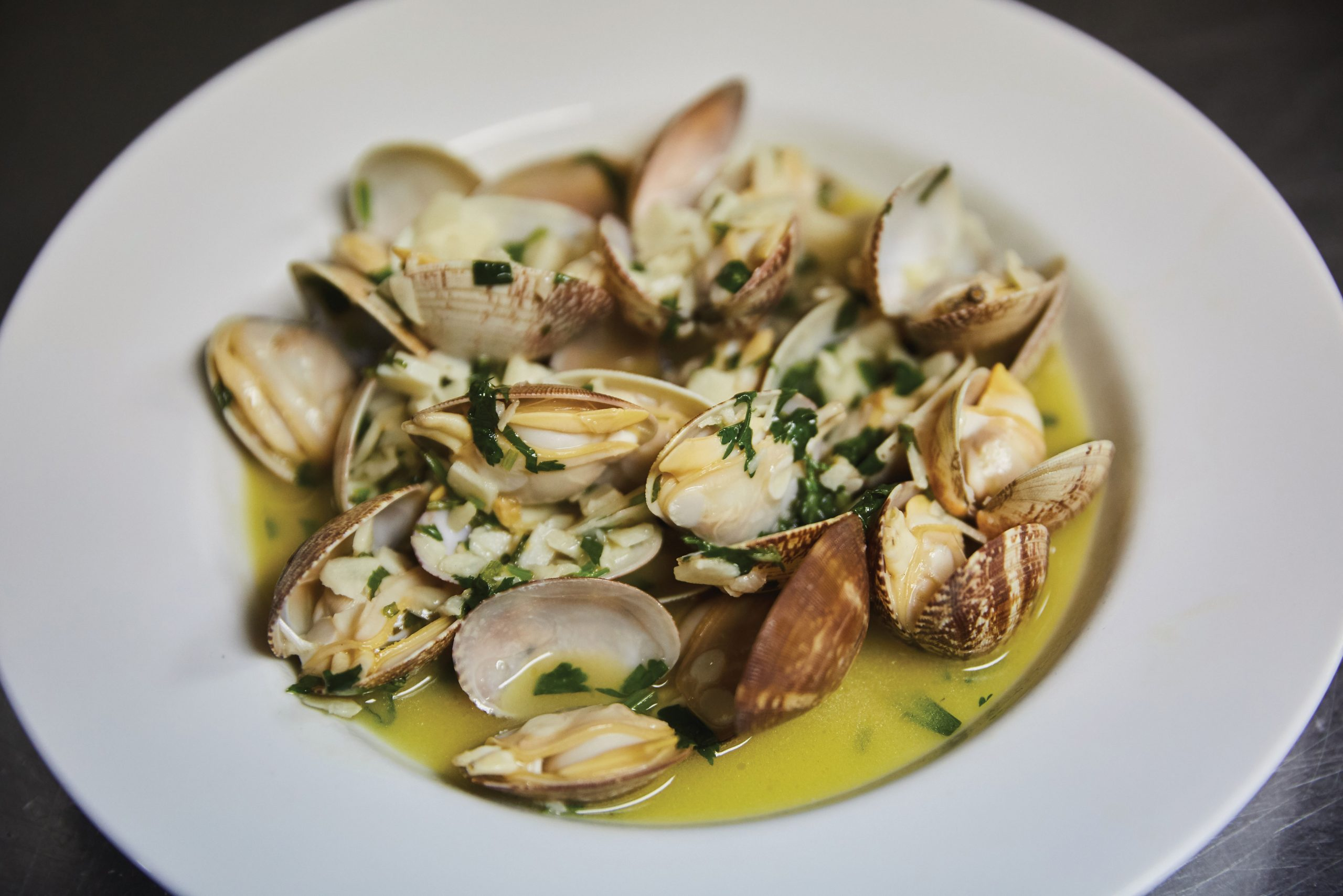 The club's version of clams with lemon and garlic in 'bulhão pato' sauce, which uses fresh coriander as a main ingredient - Photo by António Sanmarful