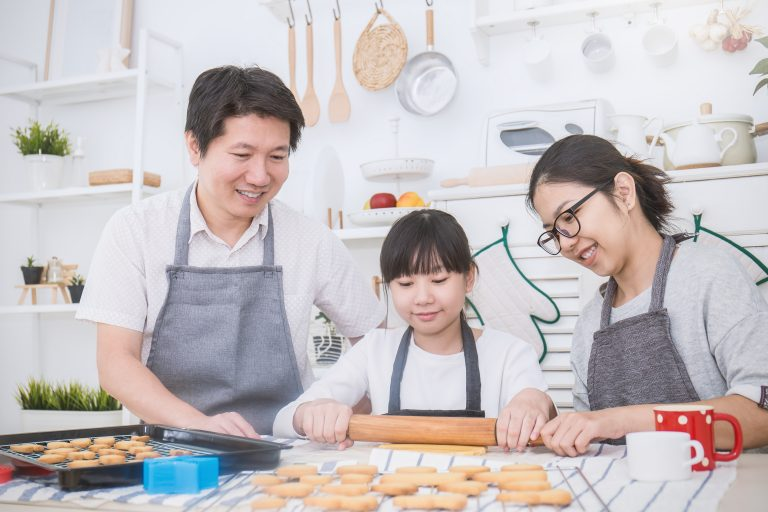 Portrait Of Little Asian Girl And Her Parents Baking Cooking
