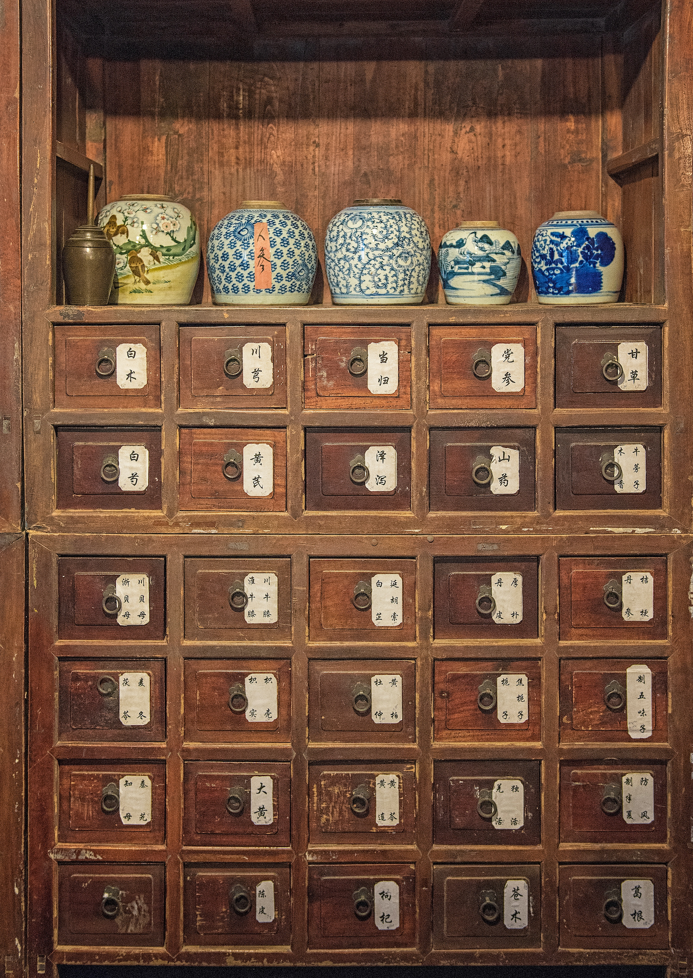 Traditional Chinese Medicine remedies inside a pharmacist's old cabinet