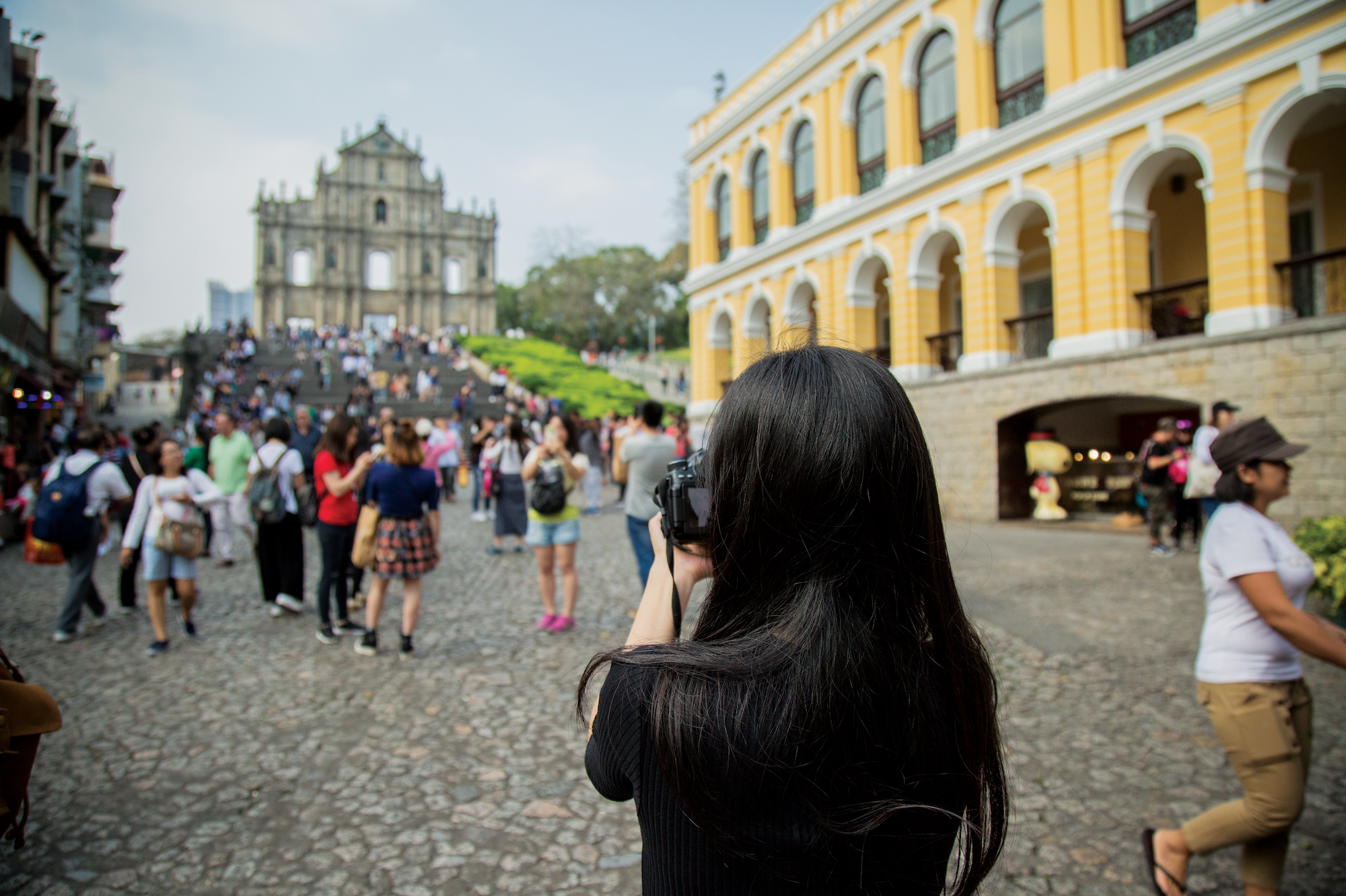 girl taking photo of the Ruins of St Paul